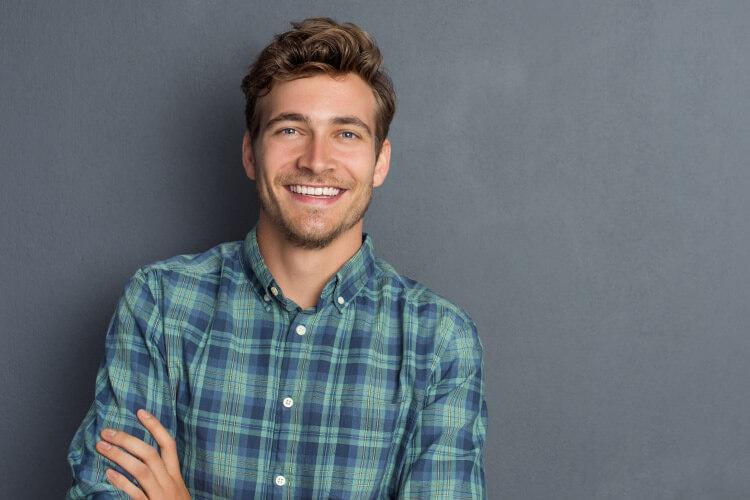 Man wearing a plaid shirt smiles after receiving a same-day CEREC dental crown restoration